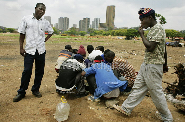 Pretoria, South Africa. Refugees from Zimbabwe near the Marabastad Refugee Reception Centre (Ministry of Home Affairs) in Pretoria where they apply for a South African visa. Because of administrative regulations and the huge amount of refugees from Zimbabwe some of these people wait for months for their visa apply. They live, cook and sleep near the ministry in the open field without any proper facilities. - Felipe Trueba - 2007-11-01