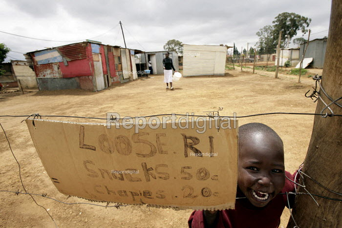 A child smiles at the camera behind a sweets shop sign in a neighbourhood in the outskirts of Johannesburg, South Africa. A large number of Zimbabweans live in these area. - Felipe Trueba - 2007-11-28