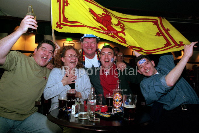 Scottish football supporters celebrate while watching the game onTV at McNeil's Bar in Glasgow. - Gerry McCann - 2002-10-08
