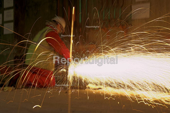 Sparks fly as a Construction worker uses an angle grinding machine - Geoff Crawford - 2006-01-25