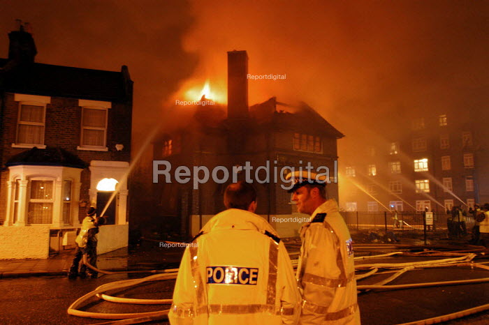 Police in attendance at a fire attended by 3 Green Goddesses manned by armed forces during the firefighters strike. The fire was at the derelict Golden Shoe pub on the notorious Kingsmead Estate in Homerton, Hackney, London. - Geoff Crawford - 2002-11-14