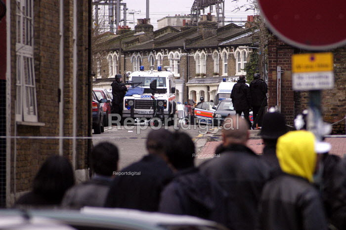 A crowd observes Police marksmen at an armed stand off at Graham Mansions, Hackney, London. - Geoff Crawford - 2002-12-27