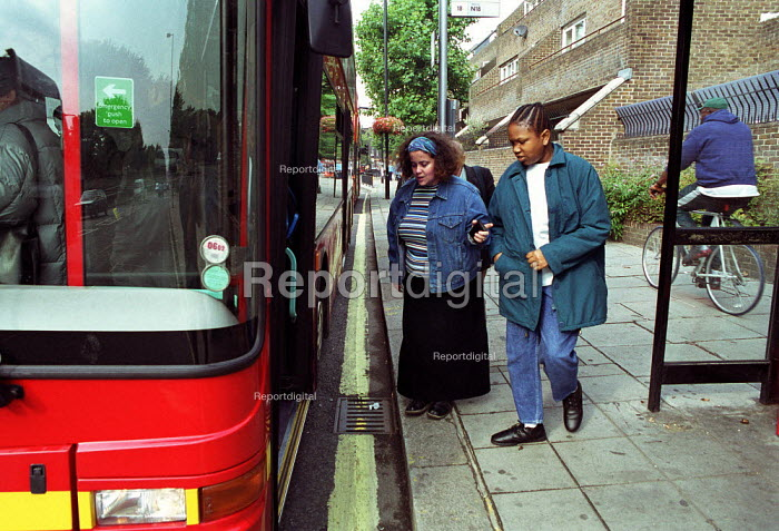 Care worker assists a disabled client at the number 18 bus stop, London. - Geoff Crawford - 2001-10-24