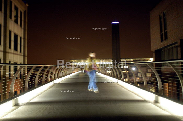 Blurry pedestrian crossing the Millennium Bridge at night with the Tate Gallery in the background. - Geoff Crawford - 2003-01-11