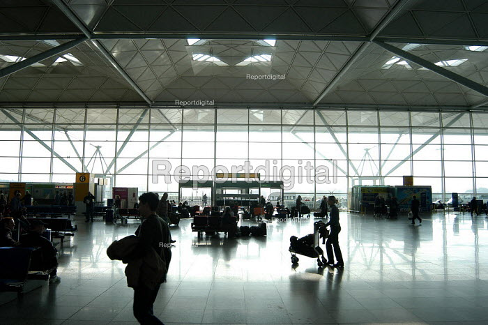 Passenger pushing a trolley in silhouette at Stansted airport terminal. - Geoff Crawford - 2003-03-22