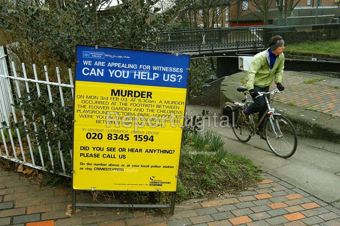 A cyclist passes an Appeal for witnesses sign at a police reconstruction of the murder of Margaret Muller, a 27 year old artist from America. Margaret was stabbed to death on 3rd of February 2003, in Victoria Park in Hackney in London. - Geoff Crawford - 2003-03-03
