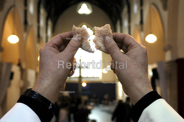Reverend Dave Tomlinson breaking the bread during holy communion at St Luke's Church Holloway, London. - Geoff Crawford - 2003-02-16