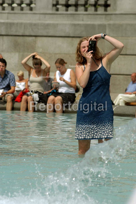 A young woman takes a photograph of her boyfriend in the fountains in Trafalgar Square, London. - Geoff Crawford - 2003-08-07