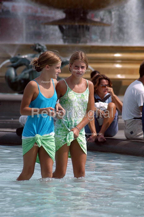 Two young girls enjoy the cooling fountains in Trafalgar Square, London. - Geoff Crawford - 2003-08-07