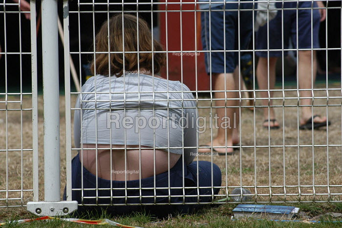A young overweight girl leans against a fence at the Bath & Wells showground - Geoff Crawford - 2003-08-11