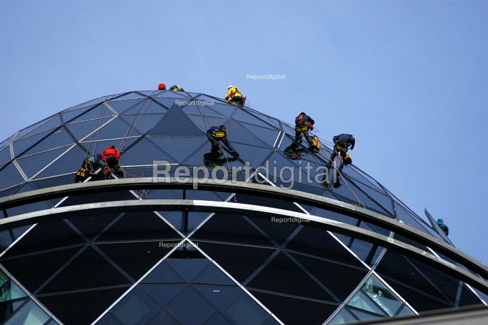 Workmen abseiling down the roof of the Swiss Re building. On the site of the Baltic Exchange at 30 St Mary Axe, the 40 floor building stands 590 ft/179.8 metres high. - Geoff Crawford - 2004-01-15