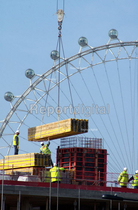 A crane carries a load of wooden boards to a construction site in Southwark south London. The British Airways London Eye is in the background. - Geoff Crawford - 2005-03-17