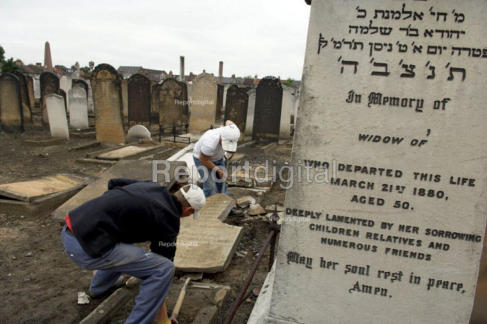 Maintenance staff repair vandalised gravestones at West Ham Jewish cemetery in Stratford, east London. Over 80 stones were pushed over and the door to the Rothschild family mausoleum was smashed in a racist attack - Geoff Crawford - 2005-06-16
