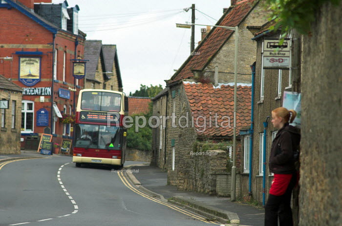 A young woman waits for a bus at a bus stop in Snainton village, North Yorkshire - Geoff Crawford - 2005-08-20
