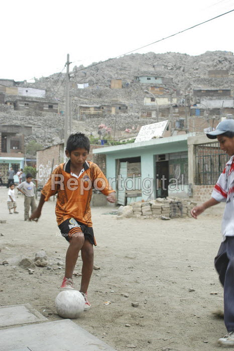 Young boys play football in a favella in Lima, Perucaption here - Geoff Crawford - 2004-02-09
