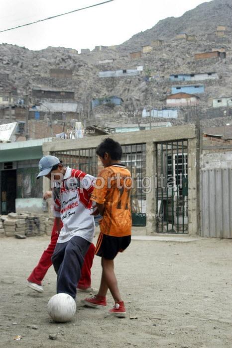 Young boys play football in a favela in Lima, Peru - Geoff Crawford - 2004-02-09