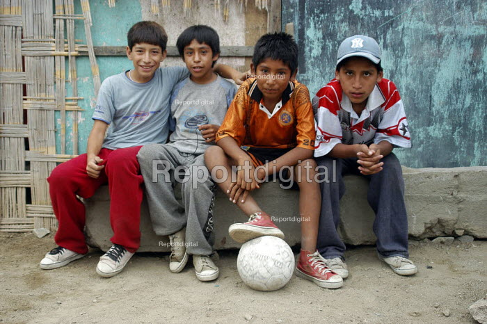 Young boys play football in a favela in Lima, Peru - Geoff Crawford - 2004-02-09