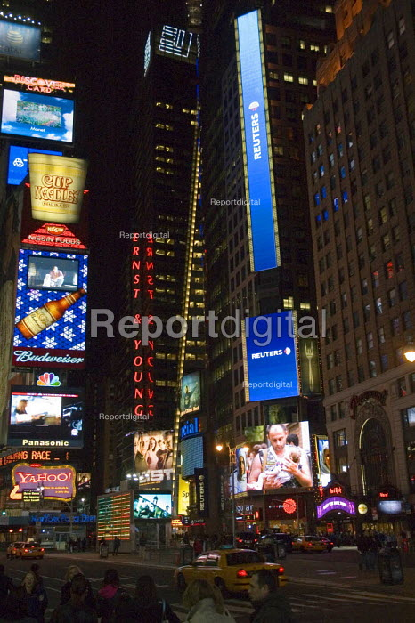 Street scene at night in Times Square, New York showing advertising and news stories on large screens. - Graham Howard - 2006-05-12