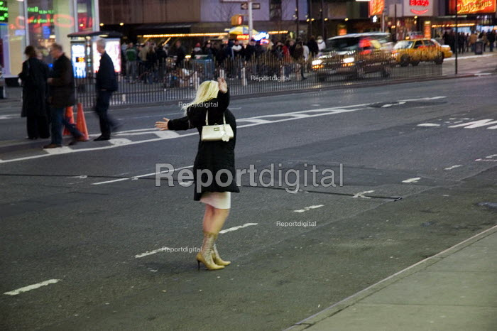 Woman hailing a taxi cab at night in Times Square, New York - Graham Howard - 2006-05-12