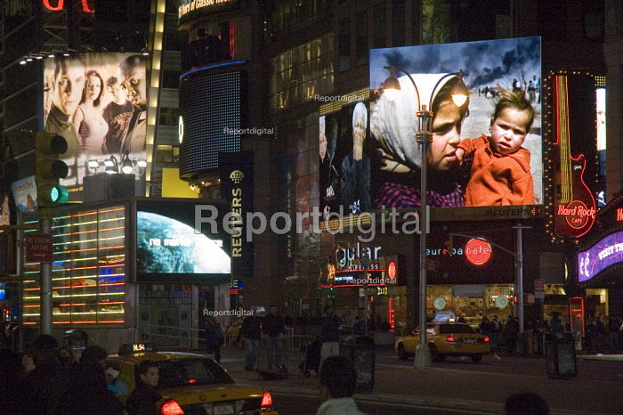 Street at night in Times Square, New York showing advertising and news stories on large screens - Graham Howard - 2006-05-12