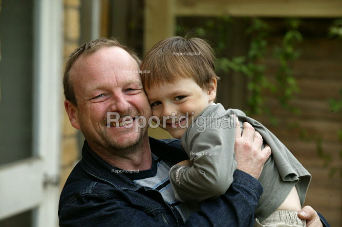 Father and son hugging. - Graham Howard - 2003-08-30