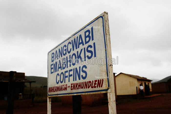 A sign for a coffin maker, near a community-based scheme in a rural shanty town to support children orphaned by AIDS and related illnesses. Organised by SWAPOL (Swaziland for Positive Living), a group of mainly women whose lives are seriously affected by HIV/AIDS. - Gerry McCann - 2005-04-25
