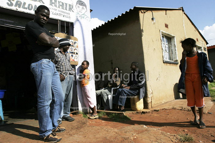 People standing outside a hairdressers, in a shanty area in Johannesburg. - Gerry McCann - 2005-04-24