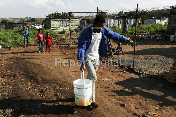 A man fetches water from the communal tap, in a shanty area in Johannesburg. - Gerry McCann - 2005-04-24
