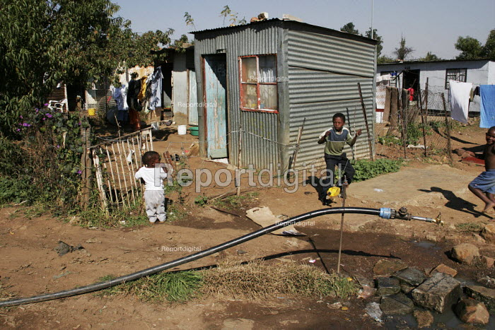 Children playing outside, in a shanty area in Johannesburg, which has a water tap to provide clean water for dozens of families. - Gerry McCann - 2005-05-08