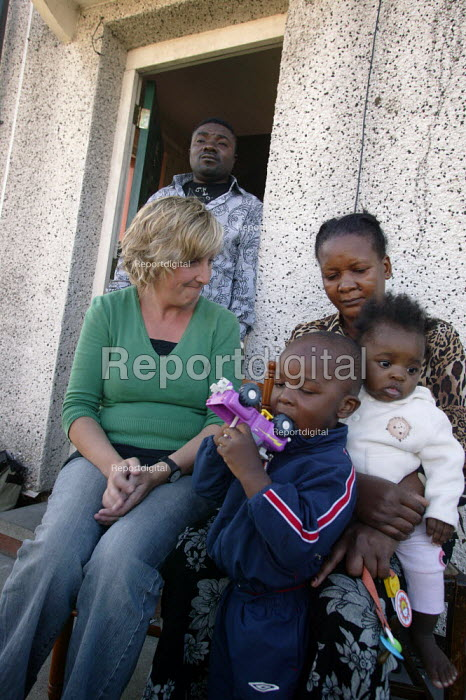 Coronation Street actress Julie Hesmondhalgh meets members of the Sukula family from the Congo, at home in Bolton, Lancashire, where they are facing eviction and their children being taken into care. They are believed to be the first under new legislation to have state support withdrawn after their asylum claim was rejected. Mother Ngiedi Lusukumu (right) is scarred from beating by Congo government militia because of her husband Kiala's (centre) links to regime opponents. - Paul Herrmann - 2005-08-10