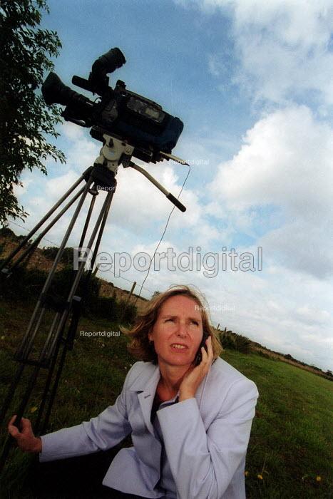Nikki Mitchell multiskilled TV presenter and camerawomen filming news story BBC South West. On mobile phone to newsdesk. - John Harris - 2002-09-06