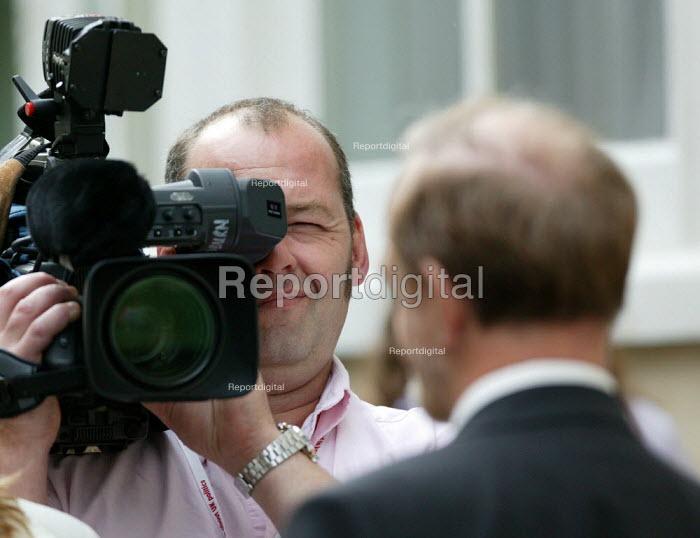 TV cameraman filming an interview. - John Harris - 2004-09-29