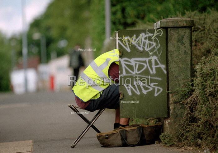 Telephone engineer repairing a junction box. - John Harris - 2001-06-28