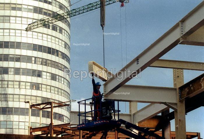 Construction worker placing girders infront of Rotunda. Redevelopment of the Bull Ring, city centre Birmingham. - John Harris - 2001-10-18