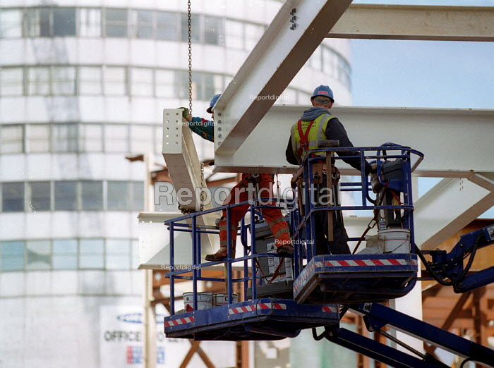 Construction workers placing girders. Redevelopment of the Bull Ring, city centre Birmingham. The Rotunda. - John Harris - 2001-10-18