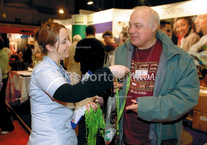 Student nurse handing out lanyards at Unison stand Labour Spring Conference Cardiff - John Harris - 2002-02-02