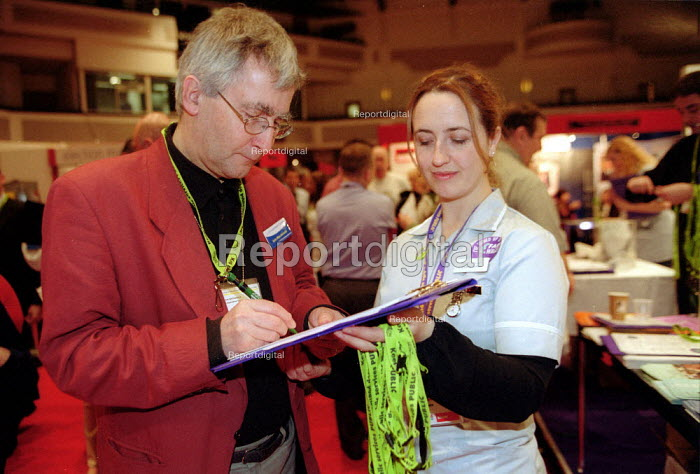 Student nurse handing out lanyards and petitioning at Unison stand Labour Spring Conference Cardiff - John Harris - 2002-02-02