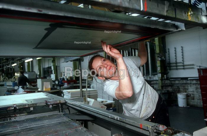 Young worker cleaning silk screen printing press, printworks. - John Harris - 2002-04-05