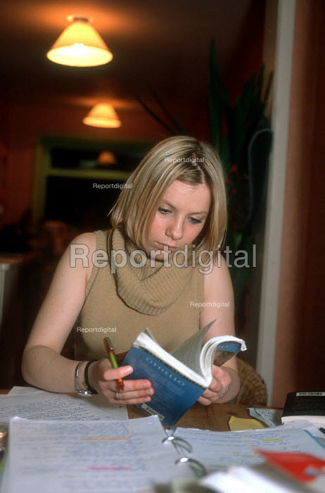 School pupil referring to an English book whilst doing her homework on a table at home after school. - John Harris - 2002-03-06