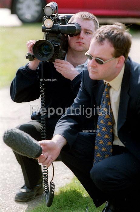 TV journalist interviewing and cameraman filming a news story. - John Harris - 2002-03-30