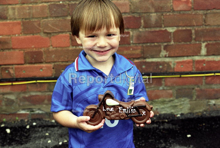 Emilio with Fathers Day gift, a chocolate motorcycle. Wearing an Italian football shirt. - John Harris - 2002-06-16