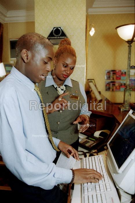 Hotel workers at Hotel reception, Grand Hotel Birmingham. Shop steward with member. - John Harris - 2002-11-02