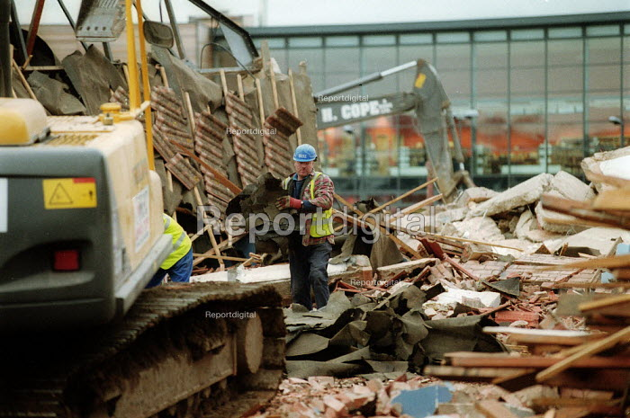Demolition worker moving debris by hand amongst mechanical diggers as the previous High School is demolished. The new school building can be seen behind, the land will be used for housing. Stratford on Avon - John Harris - 2003-03-02
