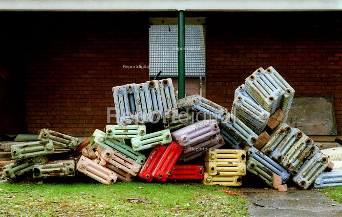 A pile of heating radiators to be recycled as the previous High School is demolished. The new school building can be seen behind, the land will be used for housing. Stratford on Avon - John Harris - 2003-03-02