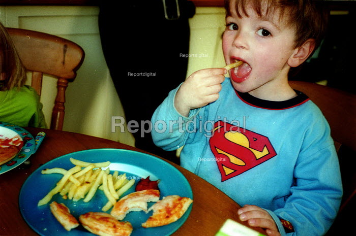 Boy eating pizza and chips. - John Harris - 2003-04-08