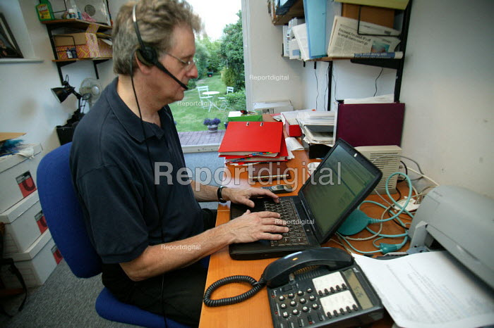 Employee teleworking from home, working with a laptop computer BT broadband internet connection and telephone headset. - John Harris - 2003-07-22