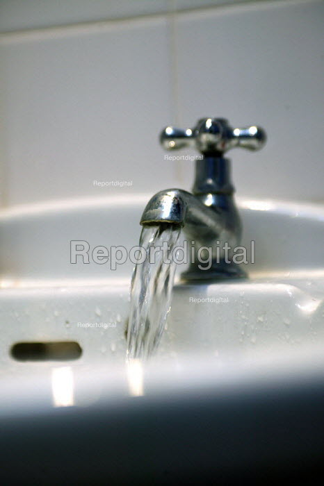 Water running from a tap into a sink in the bathroom. Fluroide is added to drinking water in this area to help prevent tooth decay. - John Harris - 2003-08-31