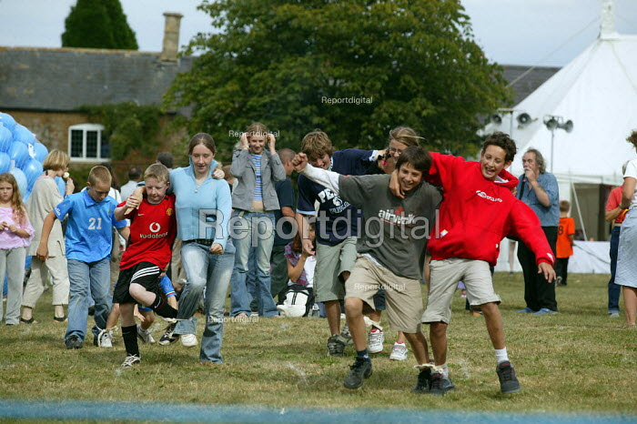 Running a three legged race on the village green, Children's Sports, Whichford Village Fete, The Cotswolds. August Bank Holiday. - John Harris - 2003-08-25