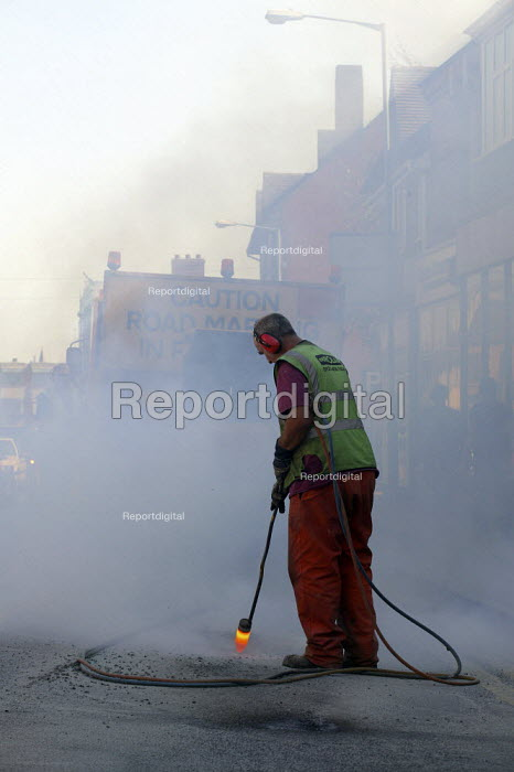 Worker from contractor Durolas removing road markings. - John Harris - 2003-09-17