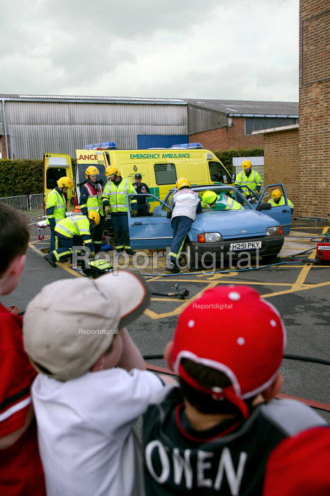 Children watching an emergency services attend a simulated road traffic accident at a fire and ambulance station open day. They are cutting open the car to get a victim out. - John Harris - 2003-09-20